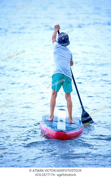 boy doing Stand up paddle on the seaside
