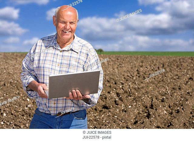 Smiling farmer using laptop in ploughed field