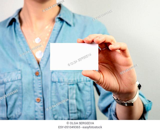 Female hand hold blank white card mockup. Plain call-card mock up template holding woman arm. Caucasian woman in casual blue denim shirt with business card...