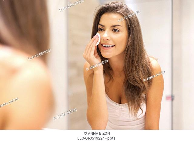 Beautiful brunette woman removing makeup from her face. Debica, Poland