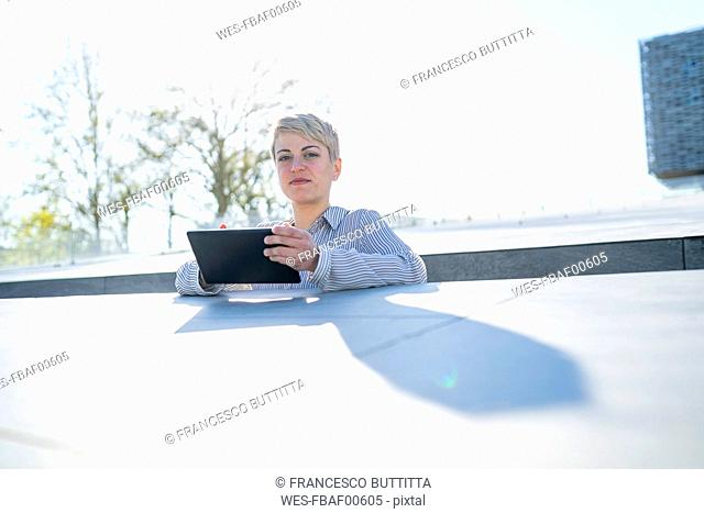 Portrait of young woman leaning on wall using digital tablet