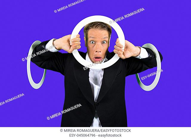 Elegant and scared juggler with three juggling rings, looking through one of them