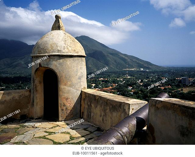 Santa Rosa Fort, corner of crenellated battlements with a cannon. View towards mountains beyond