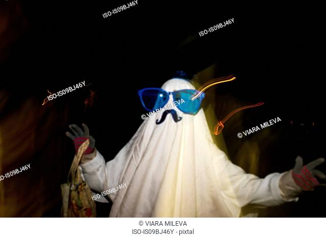 Girl dressed as ghost with mustache and over sized sunglasses, blurred