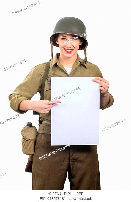 young woman dressed in wwii military us uniform with helmet showing empty blank signboard with a copyspace