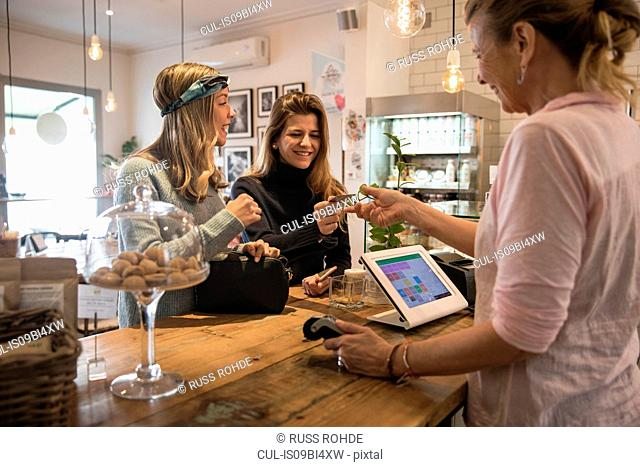 Two female friends, standing at counter in cafe, handing credit card to shop assistant for payment