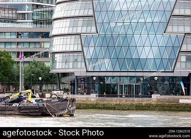 LONDON, ENGLAND - JUNE 08, 2017: Modern office buildings along river Thames with moored barges in London, England