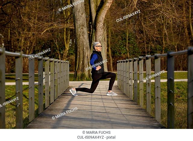 Full length side view of woman on wooden path, hands on hips lunging
