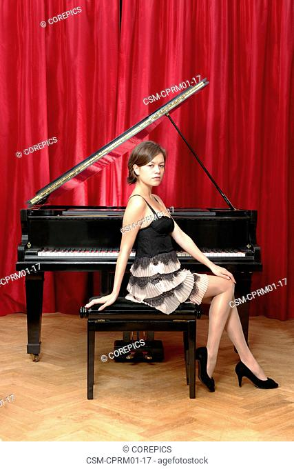 Beautiful woman, sitting sideways on a stool in front of a grand piano