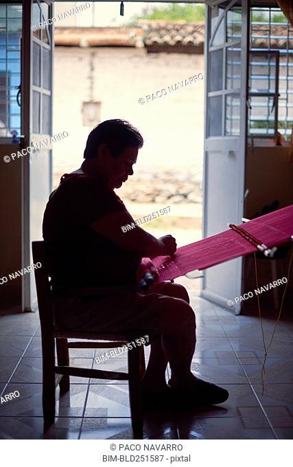 Hispanic woman weaving fabric on loom near doorway