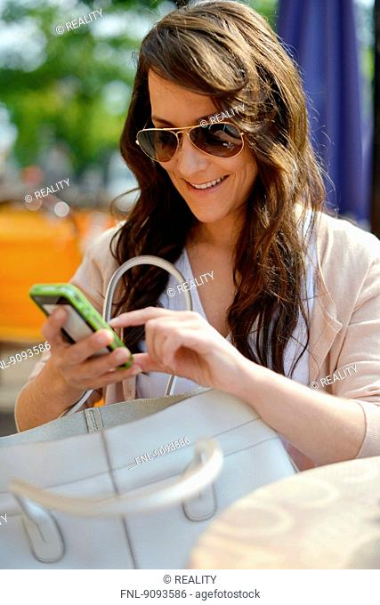 A woman with her mobile is doing some shopping in the city