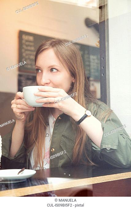 Young woman having coffee in cafe
