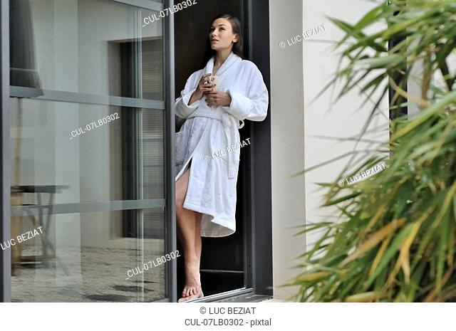 Woman relaxing by door with cup