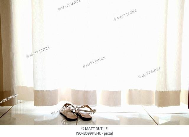 Pair of sandals by curtain