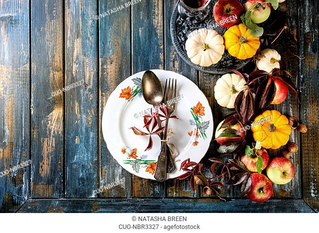 Autumn holiday table decoration setting with decorative pumpkins, apples, red leaves, empty plate with vintage cutlery over wooden table