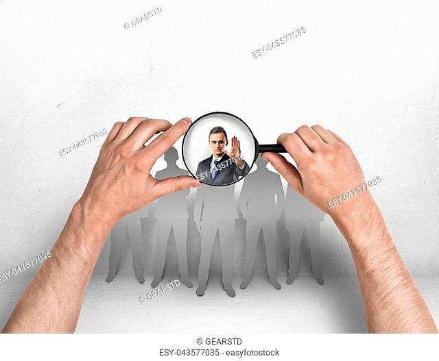 Close-up view of a man's hands focusing magnifier on a businessman with his hand raised. Body language. Stop sign. Employment issues