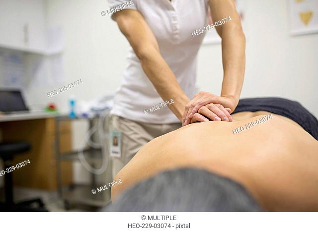 Physical therapist massaging patient back