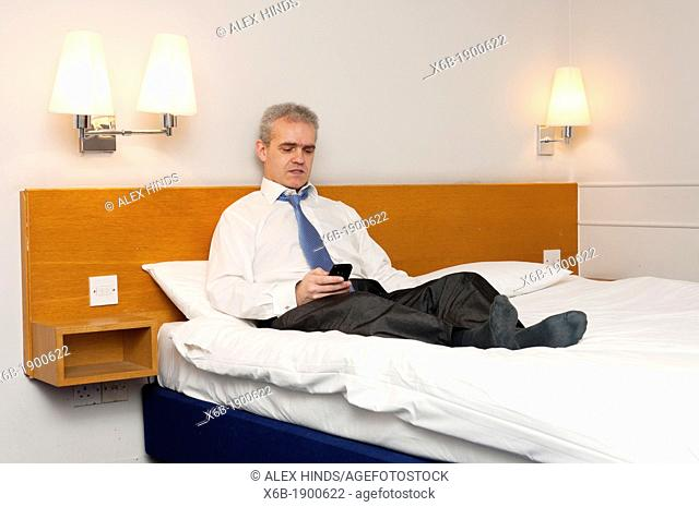 Business man sitting on hotel bed checking his phone for messages