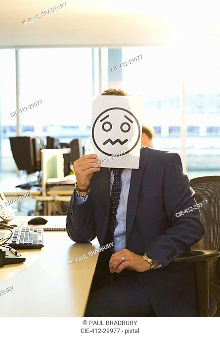Portrait of businessman holding frowning face printout over his face in office