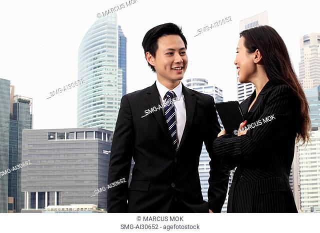 Man and woman wearing business suits smiling in front of buildings