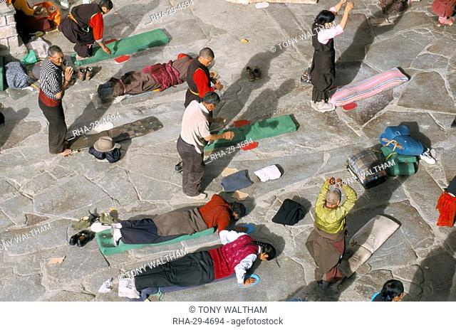 Pilgrims prostrating in front square, Jokhang Buddhist temple, Lhasa, Tibet, China, Asia