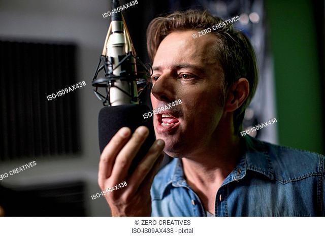 Man singing into microphone in recording studio