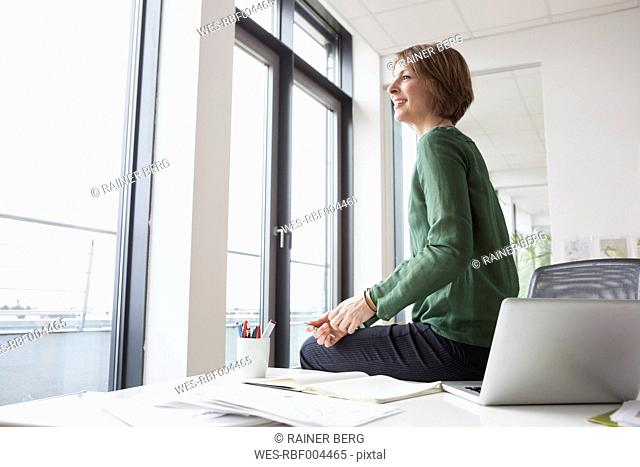 Businesswoman on office desk looking out of window