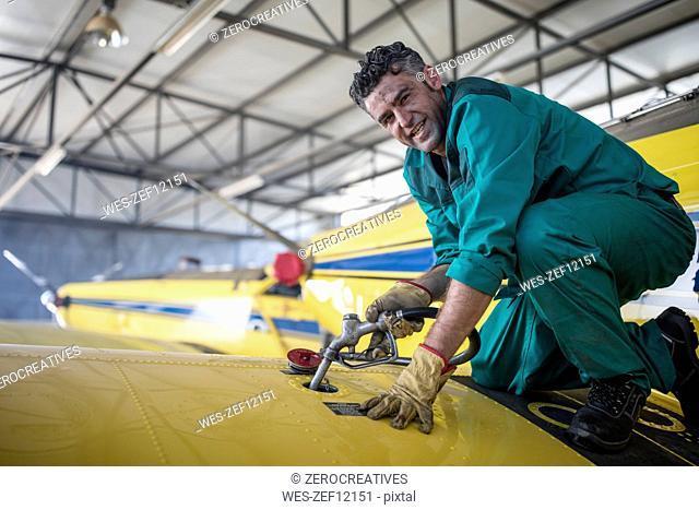 Mechanic in hangar refilling tank of light aircraft