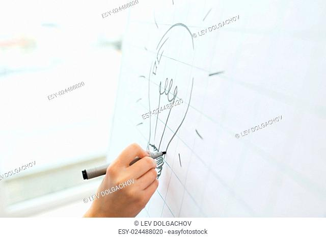 business, people, idea, startup and education concept - close up of hand with marker drawing light bulb on flip chart at office
