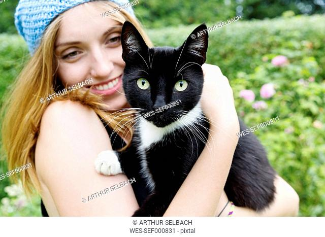 Portrait of a smiling young woman holding cat on her arms