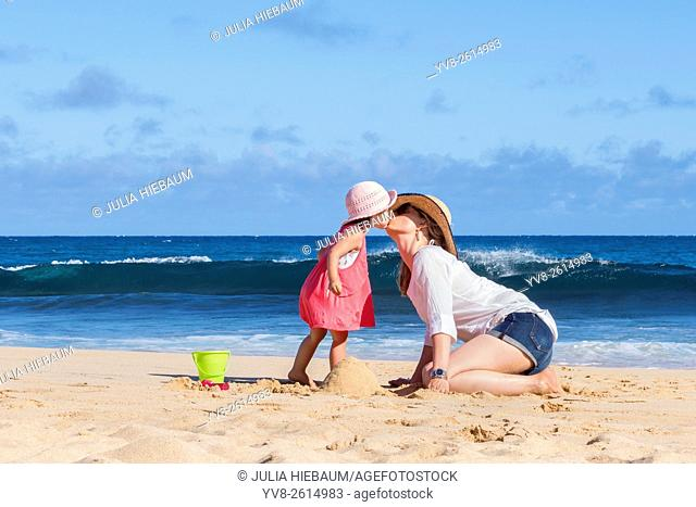 Mother and daughter kissing on the beach, Kauai island