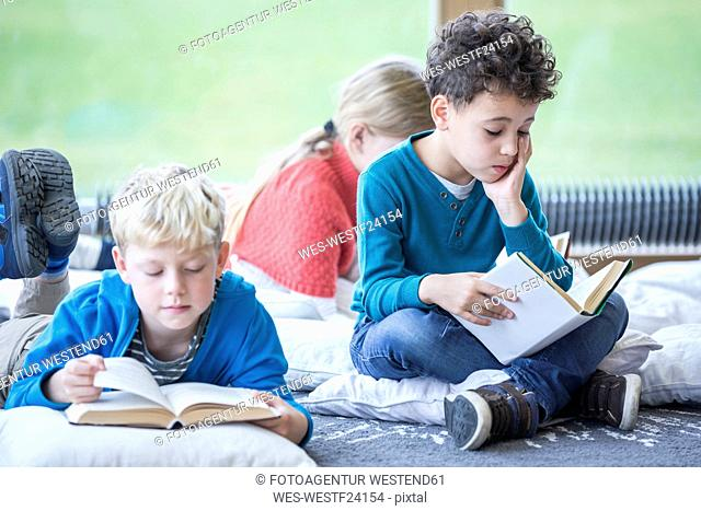 Pupils reading books on the floor in school break room