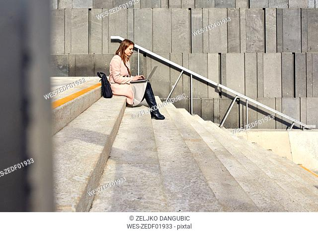 Austria, Vienna, young woman sitting on stairs at MuseumsQuartier using laptop