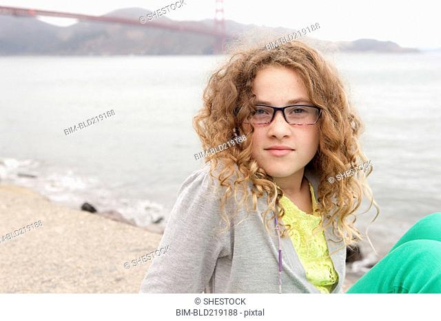 Caucasian girl sitting on beach near Golden Gate Bridge, San Francisco, California, United States