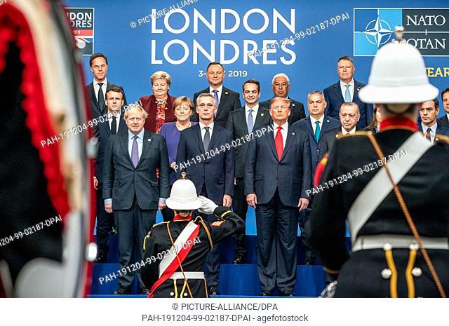 04 December 2019, Great Britain, Watford: A soldier salutes Boris Johnson (front l-r), Prime Minister of Great Britain, Jens Stoltenberg, NATO Secretary General