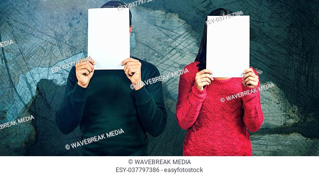 Composite image of couple hiding faces with blank papers