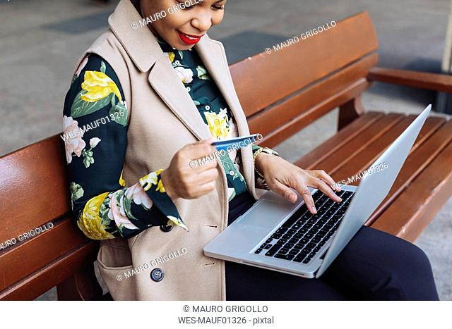 Businesswoman sitting on bench using laptop and credit card