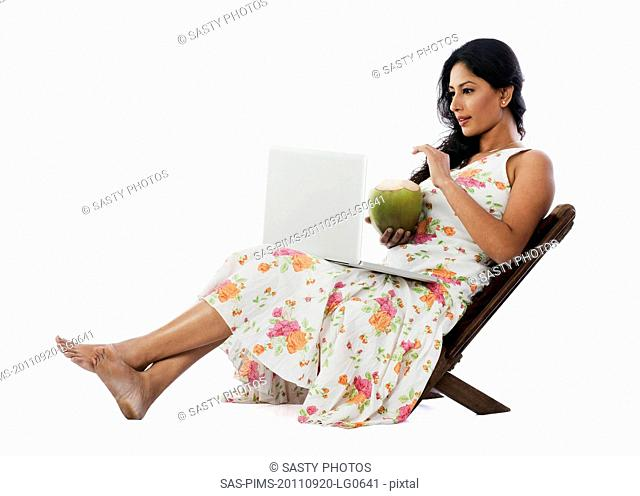 Woman drinking coconut milk and using a laptop