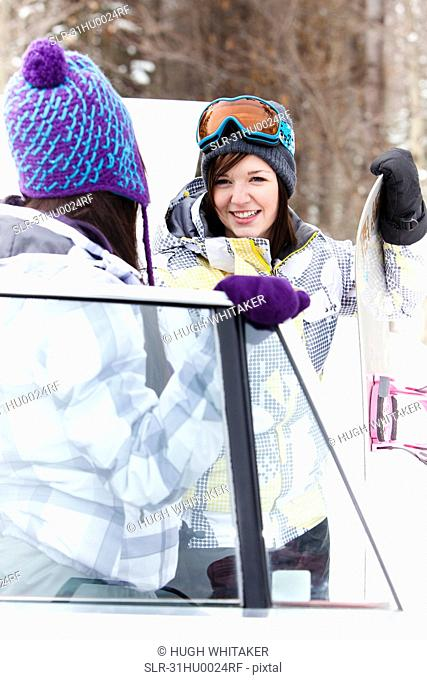 Teen girls by car with snowboard