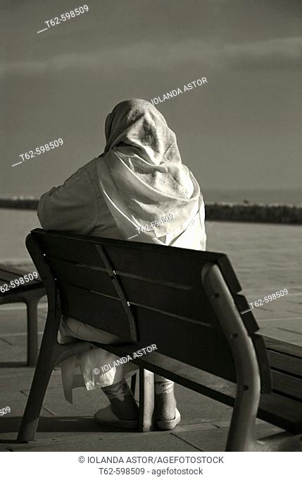 Muslim woman sitting in front of the sea