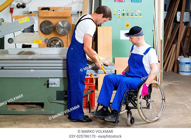 disabled worker in wheelchair in a carpenter's workshop with his colleague