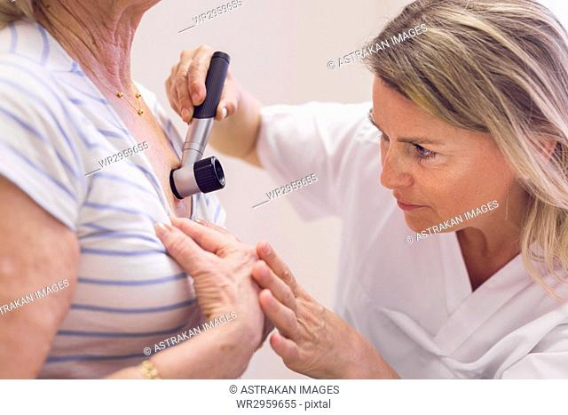 Doctor examining senior woman's skin