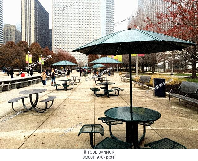 Table, chairs and sunshade. Chase Promenade Central. Millennium Park Chicago Illinois USA