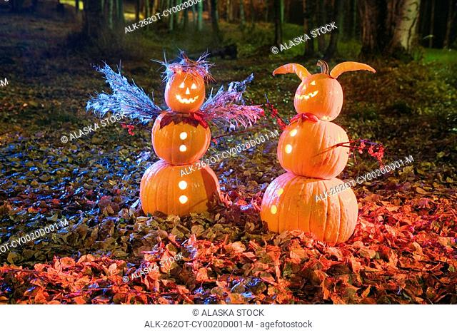 Two Jack-O-Lantern people, one angel & one devil, standing in a forest & fallen leaves on the ground at twilight during Fall in Anchorage, Alaska