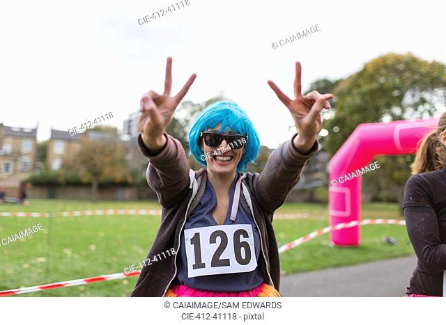 Portrait enthusiastic female runner in wig gesturing peace sign at charity run in park