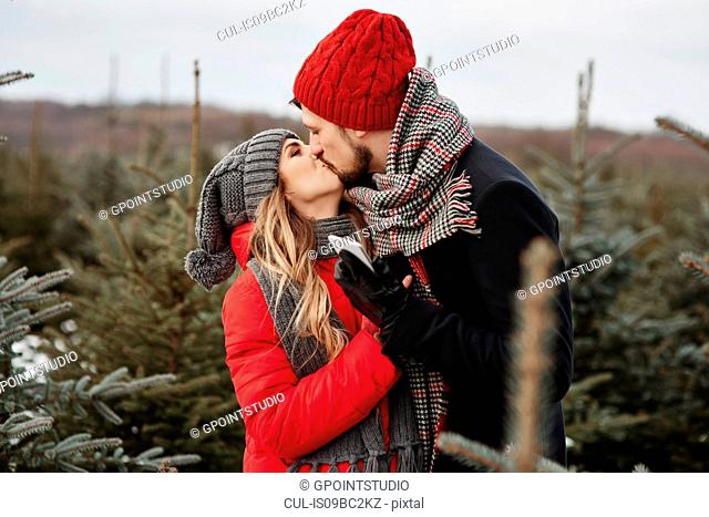 Romantic young couple kissing while shopping for christmas tree from forest