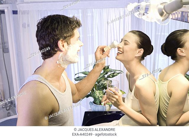 Young man applying shaving cream to young woman