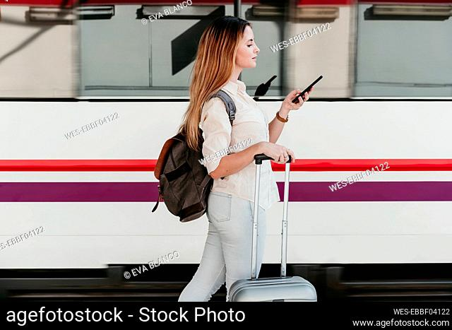Young woman wearing backpack using smart phone walking at railroad station