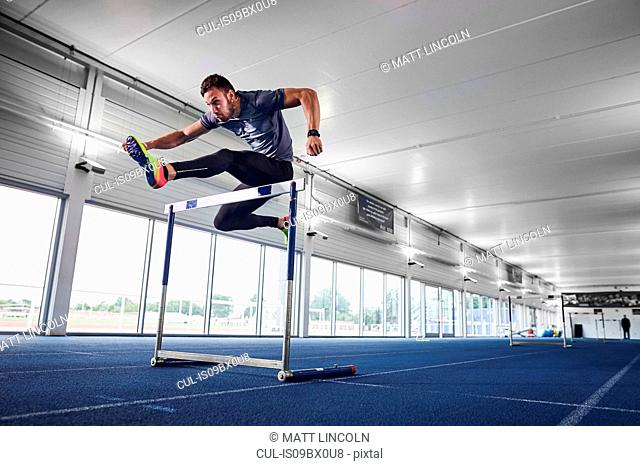 Athlete jumping over hurdle on indoor running track