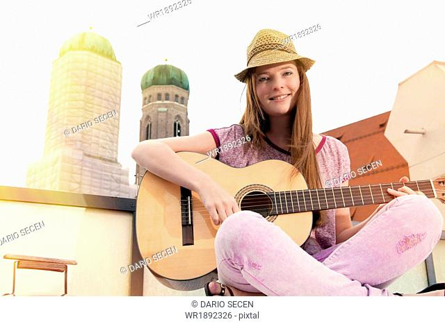 Young woman playing guitar on balcony, Munich, Bavaria, Germany